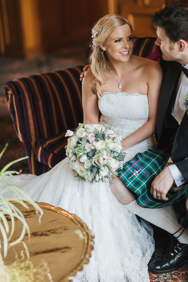 bride and groom sitting inside lochgreen hotel