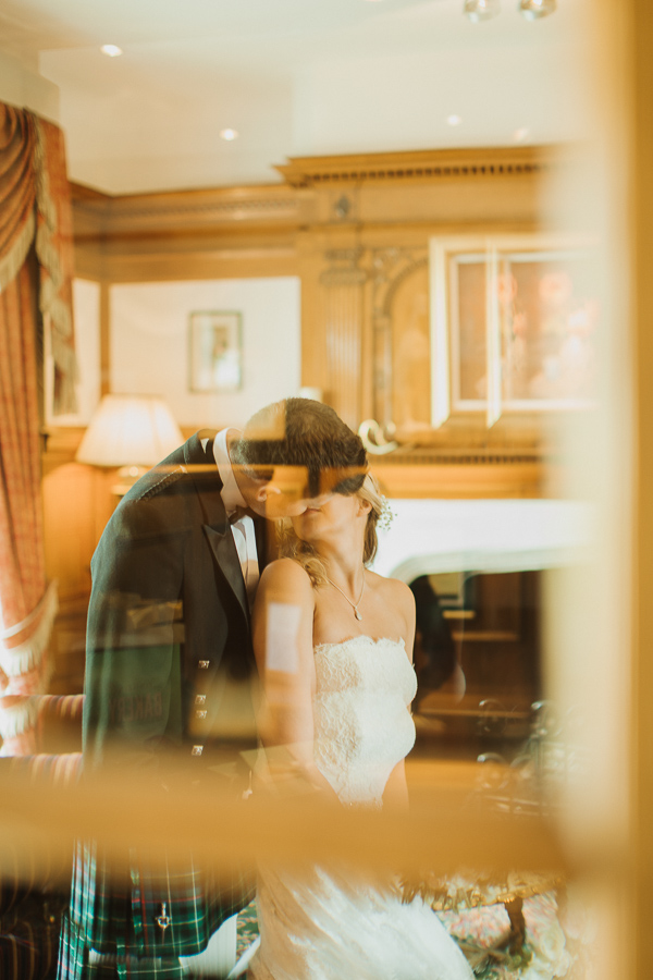 view through window bride and groom kissing