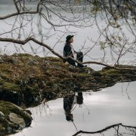 girl sitting on the edge of lake with reflexion scotland