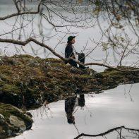 girl sitting on the edge of lake with reflexion scotland