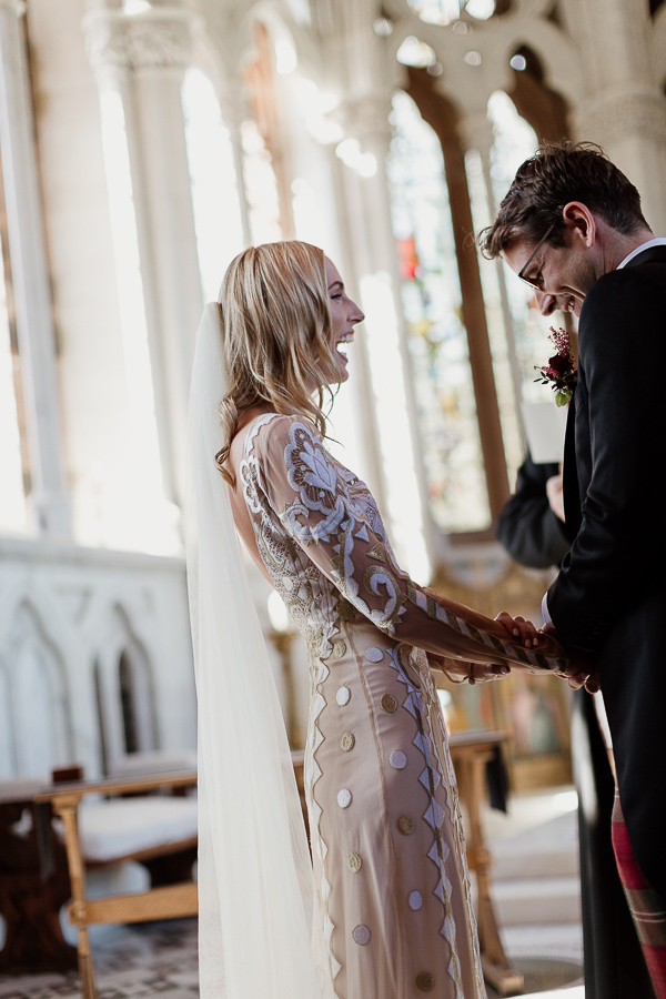 lauging and holdign hands during wedding ceremony