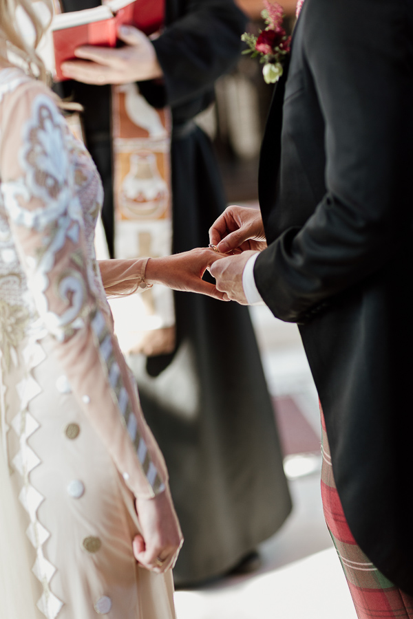 groom putting ring on brides finger scotland