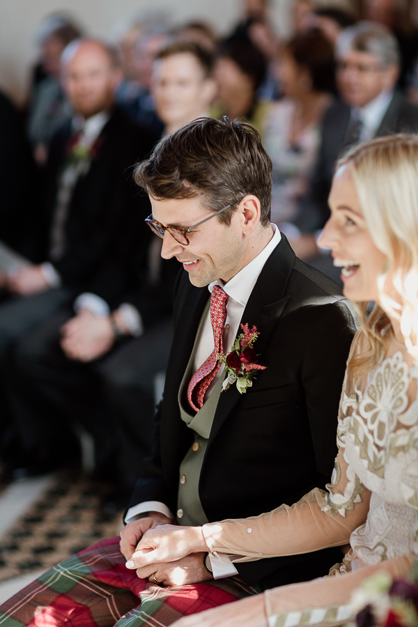 groom and bride smiling during church ceremony