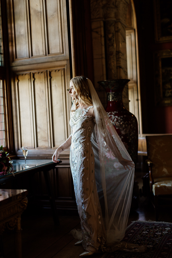 bride spreading her veil looking through the window
