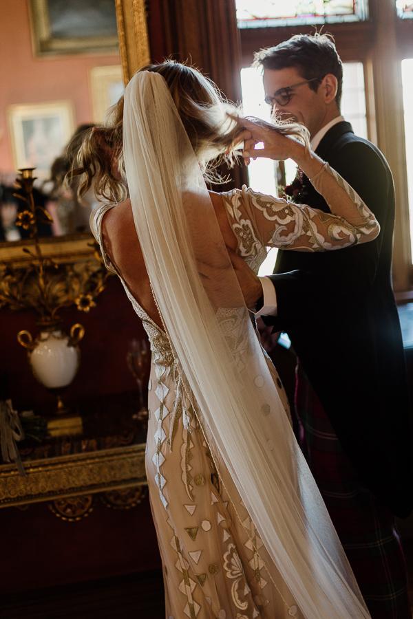 bride fixing her hair groom holding her