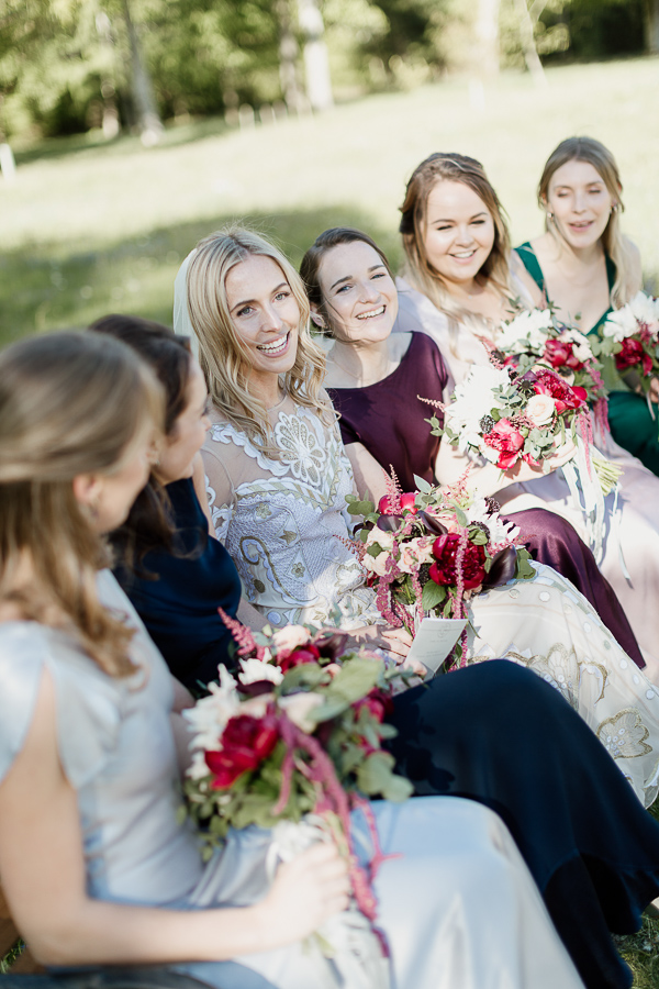 bride with friends sitting on a bench