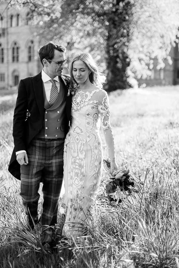 bride and groom walking in teh garden in scotland