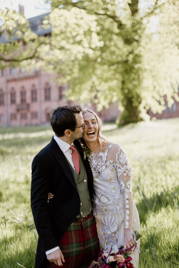 bride and groom kissing and laughing in the garden of mount stuart