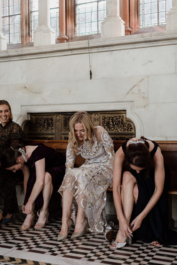 bride with bridesmates putting their shoes on