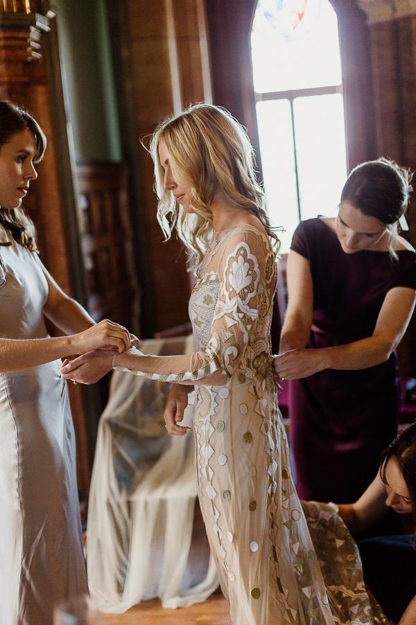 bride putting dress on bridesmates helping