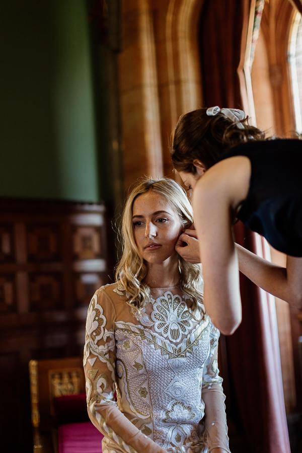 bridesmate putting earling on bride