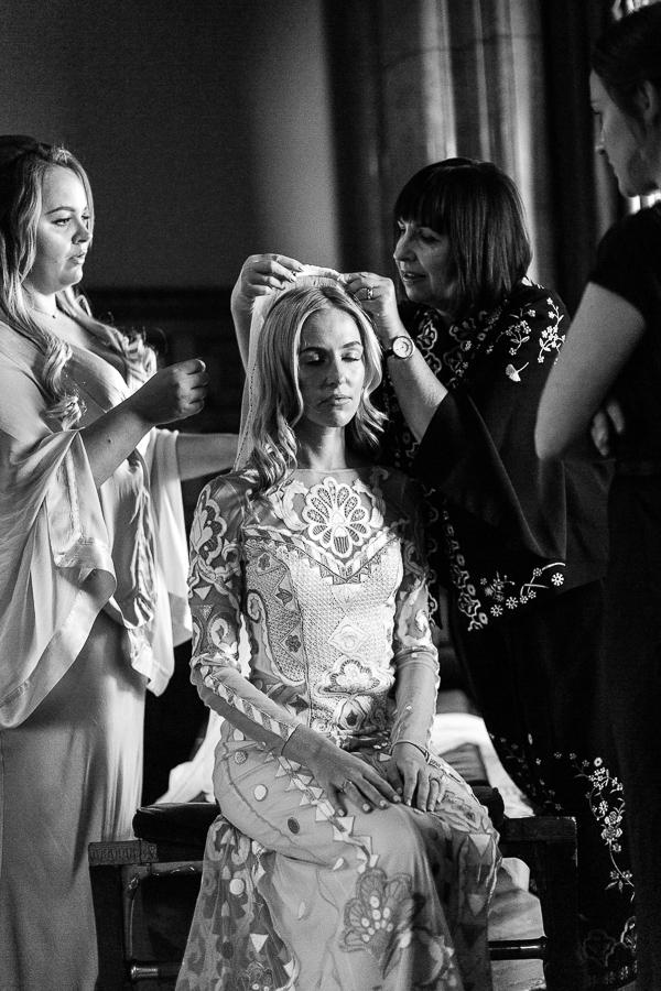 mom mounting veil on daughters hair wedding