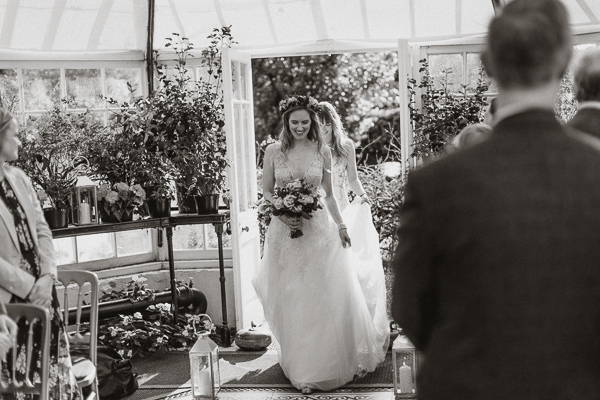 bride walking into a green house atGlenapp Castle for a humanist ceremony