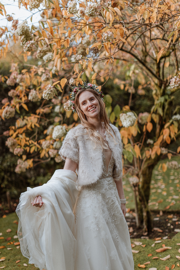 bride holding her dress by the tree at Glenapp Castle Scotland