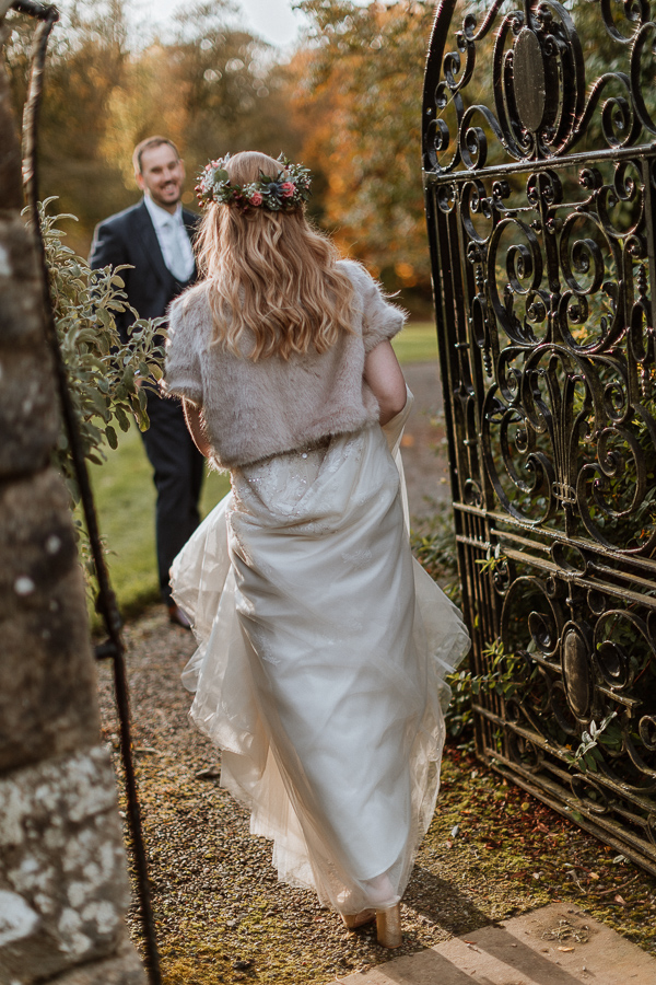 bride waking through a gate of Glenapp Estate
