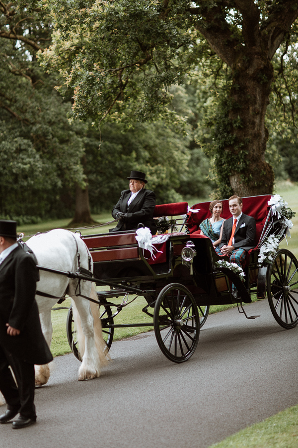 bride and groom arriving to soarn castle with a carriage