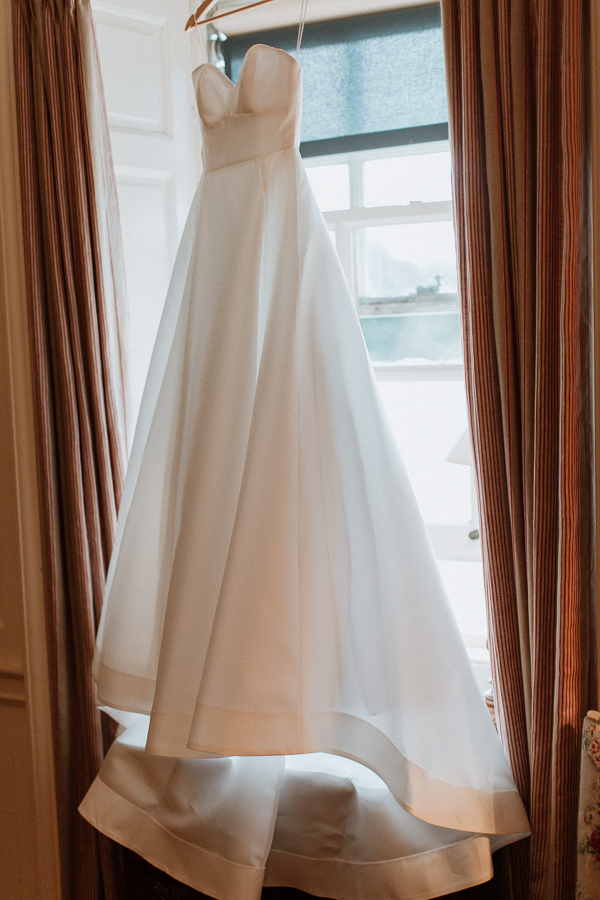 wedding dress hanging on a window at dumfries house