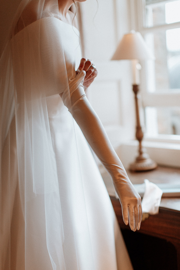 bride putting her long wedding gloves