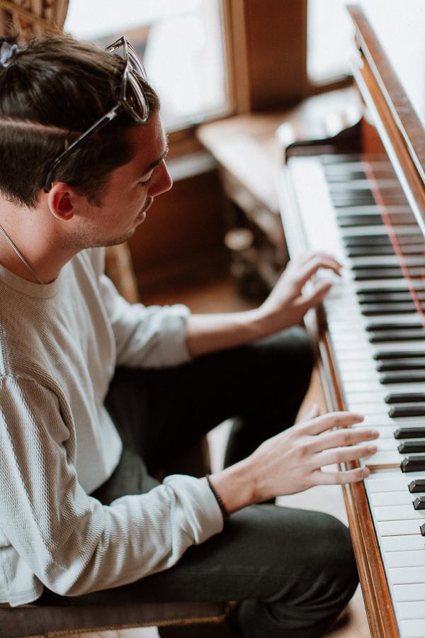 groomsman playing piano during preparations