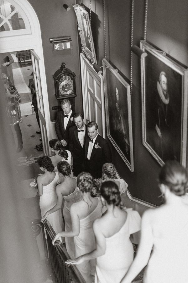 groom looking at bridesmates walking down